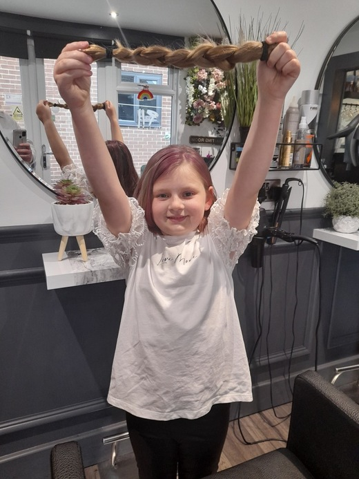 Main image for Hetty's long locks chopped off for kids' cancer charity